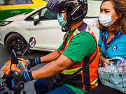 31 JANUARY 2019 - BANGKOK, THAILAND:   A motorcycle taxi driver and his passenger wearing breathing filters because of air pollution over Bangkok. The Thai government has closed more than 400 schools for the rest of the week because of high levels of pollution in Bangkok. At one point Wednesday, Bangkok had the third highest level of air pollution in the world, only Delhi, India and Lahore, Pakistan were worst. The Thai government has suspended some government construction projects and ordered other projects to take dust abatement measures. Bangkok authorities have also sprayed water into the air in especially polluted intersections to control dust. Bangkok's AQI (Air Quality Index) Thursday morning was 180, which is considered unhealthy for all people.     PHOTO BY JACK KURTZ