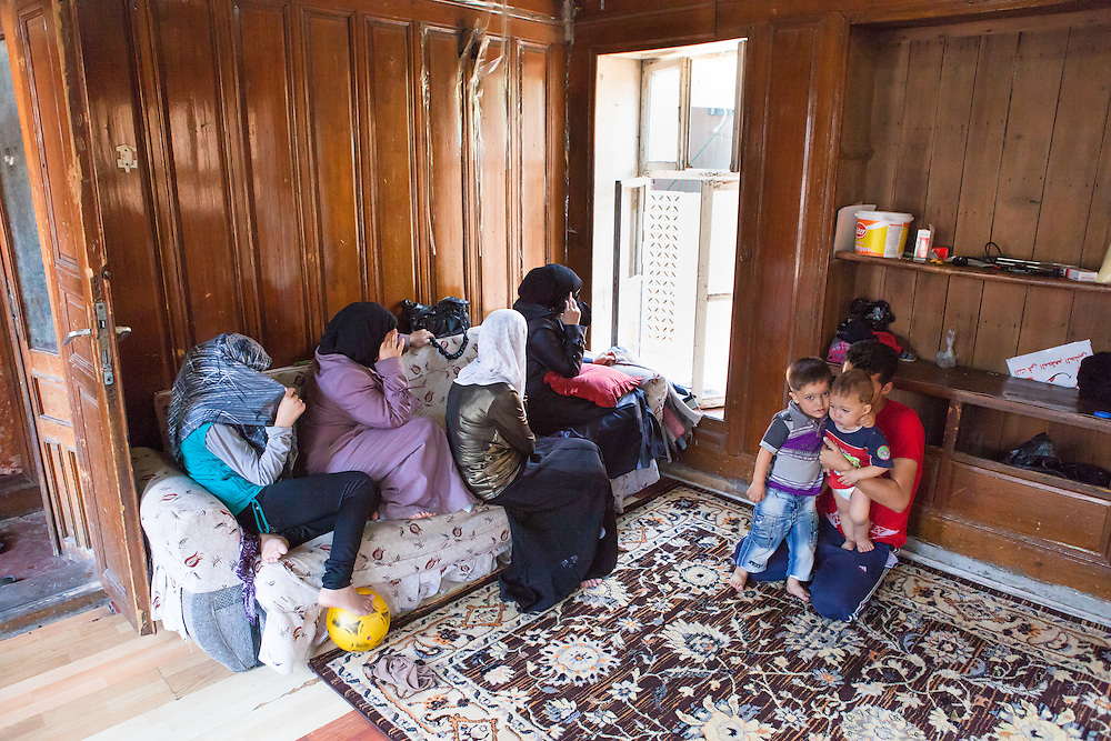 A Syrian family, originally from Aleppo, posing anonymously in their home in Gaziantep, Turkey.