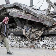 """Shejaya, quartiere a nord della striscia di Gaza. Una delle zone piu colpite dall'attacco israeliano """"Margine protettivo"""". Il quartiere è stato raso al suolo. La popolazione, a distanza di sei mesi dalla fine della guerra, vive tra le macerie della propria casa, al freddo, senza luce, gas e acqua. Nella foto un uomo cammina in quello che è rimasto di una strada di Shejaya, ai bordi solo macerie."""