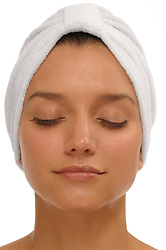 Beautiful young woman looking relaxed, eyes closed wearing a white spa turban over a white background