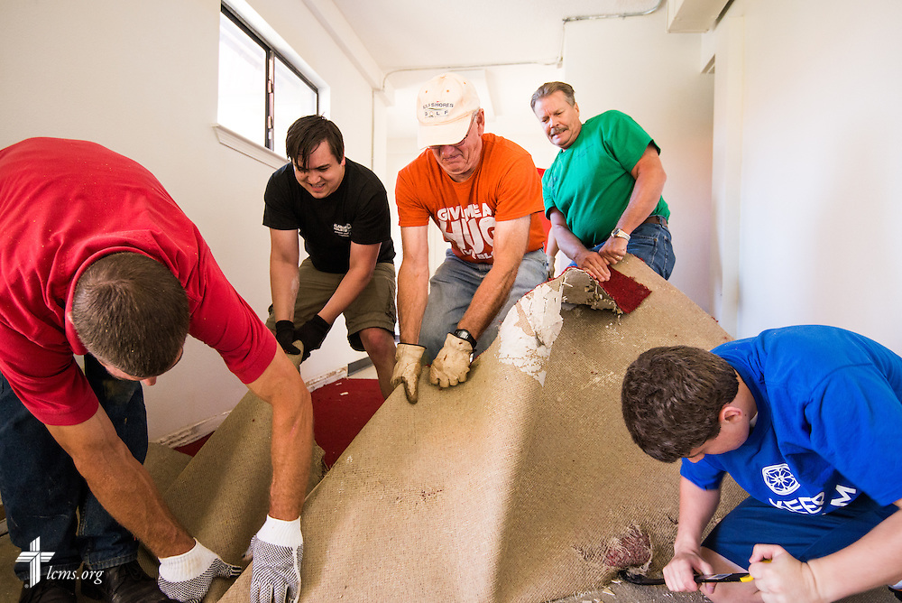 Volunteers (L-R) Matthew Jansen of St. Paul's Lutheran Church in Foley, Ala., Ben Simmons of Redeemer Lutheran Church in Fairhope, Ala., Mike Dunham, also of St. Paul's, John Butler of Good Shepherd Lutheran Church in Gulf Breeze, Fla., and John Parsons of Redeemer tear out damaged carpet in the fellowship hall of St. Matthew Lutheran Church on Saturday, May 3, 2014, in Pensacola, Fla., Torrential rainfall led to widespread flooding in the area, damaging the fellowship hall and sanctuary of the church. LCMS Communications/Erik M. Lunsford