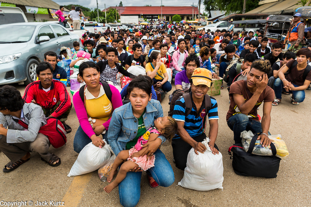 16 JUNE 2014 - ARANYAPRATHET, THAILAND:  Cambodian migrant workers returning to Cambodia sit on the ground in front of the Aranyaprathet, Thailand, train station. The Cambodians were marched from the train station to the immigration police station in Aranyaprathet where they were processed and returned to Cambodia. More than 150,000 Cambodian migrant workers and their families have left Thailand since June 12. The exodus started when rumors circulated in the Cambodian migrant community that the Thai junta was going to crack down on undocumented workers. About 40,000 Cambodians were expected to return to Cambodia today. The mass exodus has stressed resources on both sides of the Thai/Cambodian border. The Cambodian town of Poipet has been over run with returning migrants. On the Thai side, in Aranyaprathet, the bus and train station has been flooded with Cambodians taking all of their possessions back to Cambodia. PHOTO BY JACK KURTZ