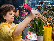 "21 DECEMBER 2015 - BANGKOK, THAILAND:  A woman lights incense to make merit during the annual rededication of a Buddhist shrine in Pak Khlong Talat, also called the Flower Market. The market has been a Bangkok landmark for more than 50 years and is the largest wholesale flower market in Bangkok. A recent renovation resulted in many stalls being closed to make room for chain restaurants to attract tourists. Now Bangkok city officials are threatening to evict sidewalk vendors who line the outside of the market. Evicting the sidewalk vendors is a part of a citywide effort to ""clean up"" Bangkok.      PHOTO BY JACK KURTZ"