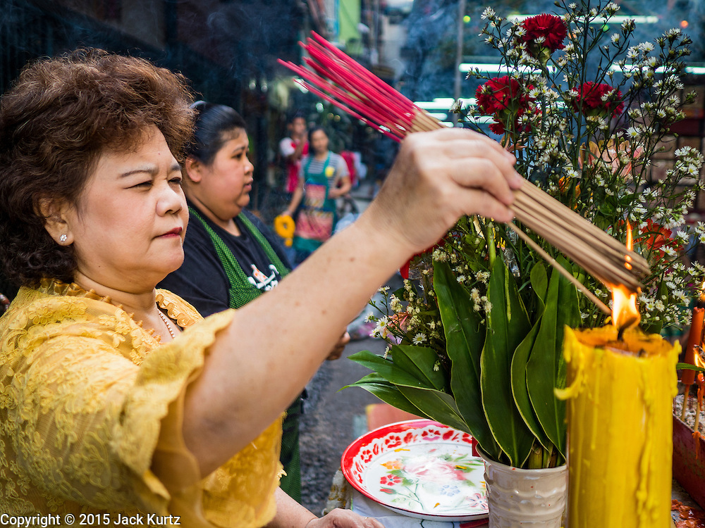 """21 DECEMBER 2015 - BANGKOK, THAILAND:  A woman lights incense to make merit during the annual rededication of a Buddhist shrine in Pak Khlong Talat, also called the Flower Market. The market has been a Bangkok landmark for more than 50 years and is the largest wholesale flower market in Bangkok. A recent renovation resulted in many stalls being closed to make room for chain restaurants to attract tourists. Now Bangkok city officials are threatening to evict sidewalk vendors who line the outside of the market. Evicting the sidewalk vendors is a part of a citywide effort to """"clean up"""" Bangkok.      PHOTO BY JACK KURTZ"""