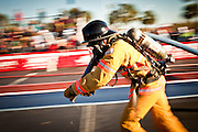A firefighter races with a fire hose while wearing full firefighting gear and working against the clock during the international finals of the Firefighter Combat Challenge on November 18, 2011 in Myrtle Beach, South Carolina.