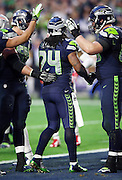 Seattle Seahawks running back Marshawn Lynch (24) gets pats on the helmet and back from teammates after scoring a second quarter touchdown that ties the score at 7-7 during the NFL Super Bowl XLIX football game against the New England Patriots on Sunday, Feb. 1, 2015 in Glendale, Ariz. The Patriots won the game 28-24. ©Paul Anthony Spinelli