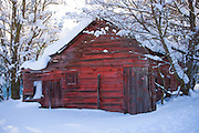 Idaho, Dalton Gardens, Coeur d' Alene. A vintage outbuilding with faded paint in a snow covered landscape. . PLEASE CONTACT US FOR DIGITAL DOWNLOAD AND PRICING.