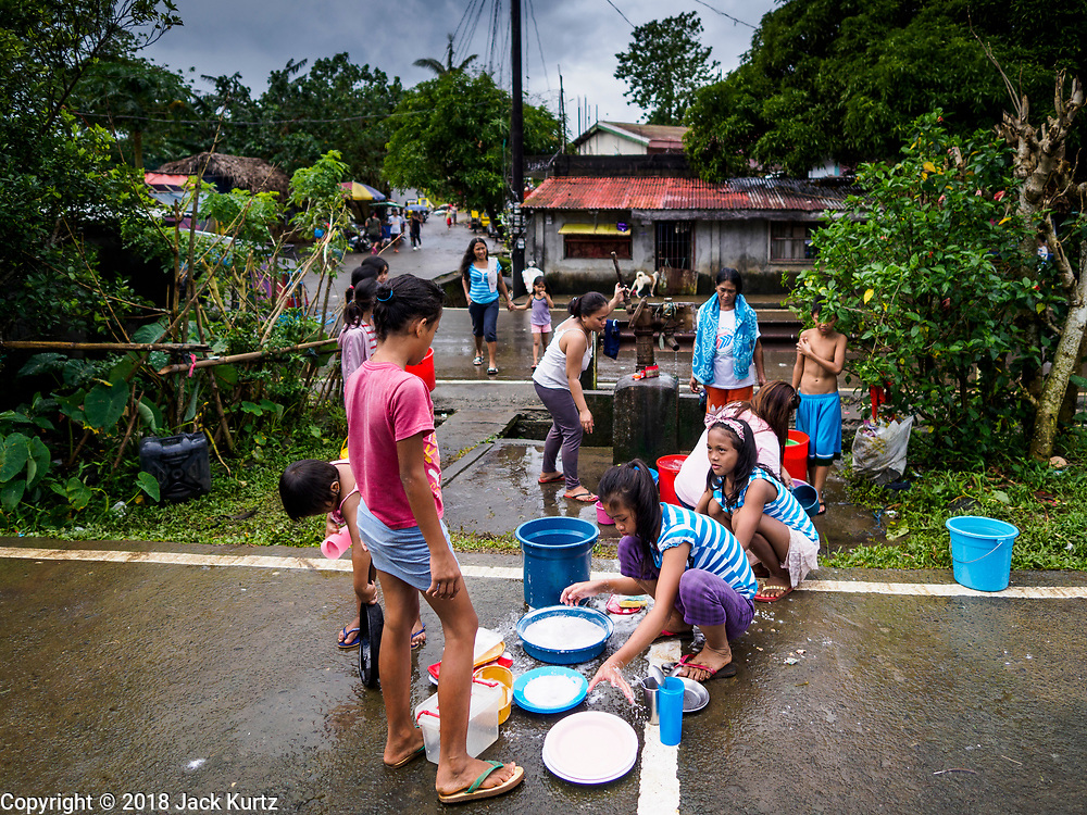 26 JANUARY 2018 - SANTO DOMINGO, ALBAY, PHILIPPINES: People evacuated from their homes on the Mayon volcano wash their clothes and dishes at a well across the street from a shelter. Mayon Volcano was relatively quiet Friday, but the number of evacuees swelled to nearly 80,000 as people left the side of  the volcano in search of safety. There are nearly 12,000 evacuees in Santo Domingo, one of the most impacted communities on the volcano. The number of evacuees is impacting the availability of shelter space. Many people in Santo Domingo, on the north side of the volcano, are sleeping in huts made from bamboo and plastic sheeting. The Philippines is now preparing to house the volcano evacuees for up to three months.        PHOTO BY JACK KURTZ