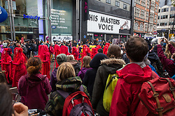 London, UK. 12 October, 2019. Shoppers in Oxford Street watch Red Brigade climate activists from Extinction Rebellion taking part in the XR funeral march from Marble Arch to Russell Square on the sixth day of International Rebellion protests to demand a government declaration of a climate and ecological emergency, a commitment to halting biodiversity loss and net zero carbon emissions by 2025 and for the government to create and be led by the decisions of a Citizens' Assembly on climate and ecological justice. Credit: Mark Kerrison/Alamy Live News