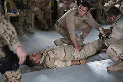 © Licensed to London News Pictures. 30/03/2015. Erbil, Iraq. A Kurdish peshmerga fighter listens to a German Army coalition forces instructor as he practices stopping bleeding on a simulated casualty during a training package being held at a military base near Erbil, Iraq.<br /> <br /> The training is part of a four week long package, the first to be held with a complete peshmerga battalion, run by coalition forces mobile training teams (MTT) in Kurdistan with the aim to make the peshmerga more efficient in combatting the Islamic State. Photo credit: Matt Cetti-Roberts/LNP