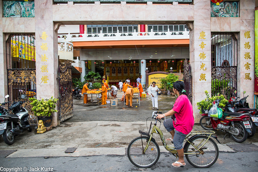 23 OCTOBER 2012 - HAT YAI, SONGKHLA, THAILAND:  A woman rides her bike past the entrance to  Wat Ta Won Vararum, a Chinese Buddhist temple in Hat Yai. The Vegetarian Festival is celebrated in Thai-Chinese communities throughout Thailand. It is the Thai Buddhist version of the The Nine Emperor Gods Festival, a nine-day Taoist celebration celebrated in the 9th lunar month of the Chinese calendar. For nine days, those who are participating in the festival dress all in white and abstain from eating meat, poultry, seafood, and dairy products. Vendors and proprietors of restaurants indicate that vegetarian food is for sale at their establishments by putting a yellow flag out with Thai characters for meatless written on it in red.   PHOTO BY JACK KURTZ