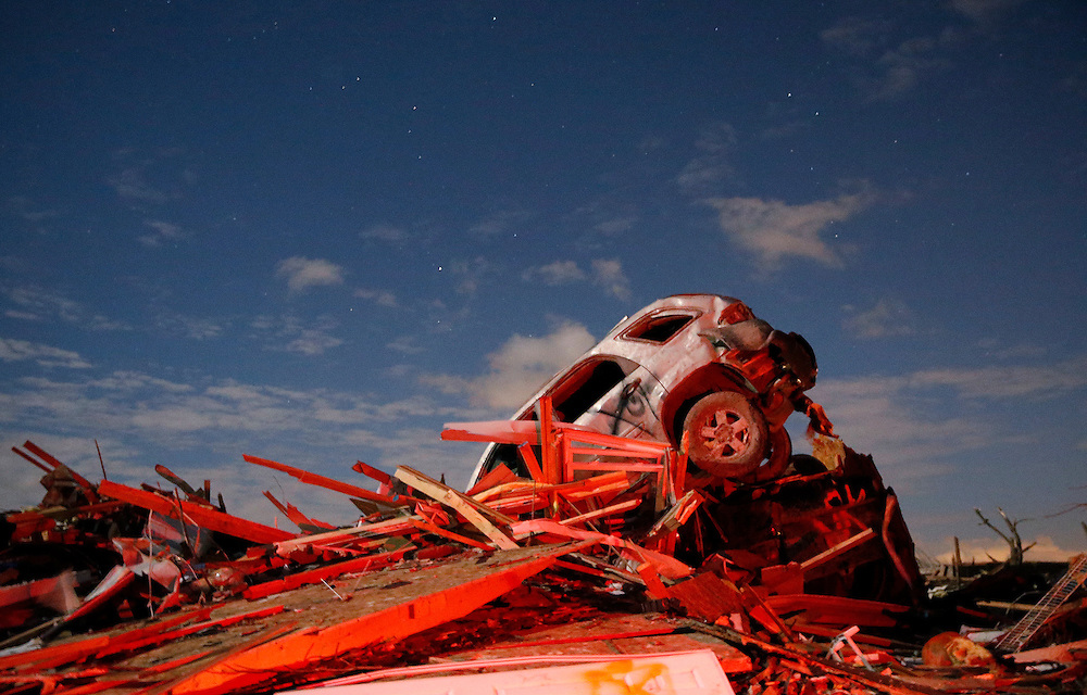 A vehicle sits on a pile of debris from the destruction caused by a tornado that touched down in Washington, Illinois, November 17, 2013.  REUTERS/Jim Young