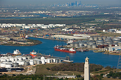 Aerial view of the Port of Houston featuring the San Jacinto Monument in the foreground and the downtown Houston skyline on the horizon.