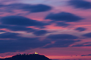 Pink sky and moving clouds above temple lit up on hilltop, Ayeyarwady River, Bagan