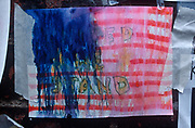 A week after the 9-11 terrorist attacks on the Twin Towers and the Pentagon, a rain-spattered poster sends a 'United We Stand' message to American patriots, on 19th September 2001, New York, USA.