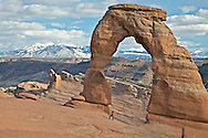 A girl poses for a photo in front of Delicate Arch, La Sal Mountains, Arches National Park, Moab, Utah