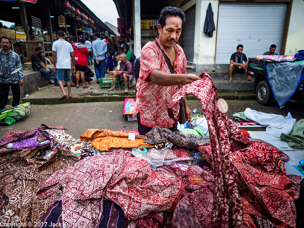 06 AUGUST 2017 - MENGWI, BALI, INDONESIA: A man sets out Indonesian batik shirts he's selling in the Bringkit Market in Mengwi, about 30 minutes from Denpasar. Bringkit Market is famous on Bali for its Sunday livestock and poultry market. Hundreds of the small Bali cows are bought and sold there every week. Bali's local markets are open on an every three day rotating schedule because venders travel from town to town. Before modern refrigeration and convenience stores became common place on Bali, markets were thriving community gatherings. Fewer people shop at markets now as more and more consumers go to convenience stores and more families have refrigerators.     PHOTO BY JACK KURTZ