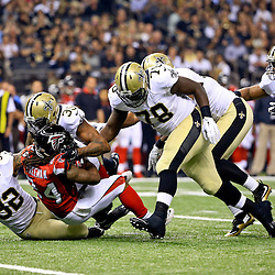 Oct 15, 2015; New Orleans, LA, USA; New Orleans Saints cornerback Brandon Browner (39) and strong safety Kenny Vaccaro (32) and defensive end Bobby Richardson (78) stop Atlanta Falcons running back Devonta Freeman (24) during the first quarter of a game at the Mercedes-Benz Superdome. Mandatory Credit: Derick E. Hingle-USA TODAY Sports