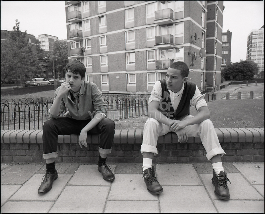 Two young men sitting on edge of short wall.
