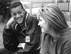 Teenage boy leaning on elbow talking to girl laughing,