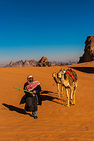 Bedouin man in the Arabian Desert with his camels, Wadi Rum, Jordan.