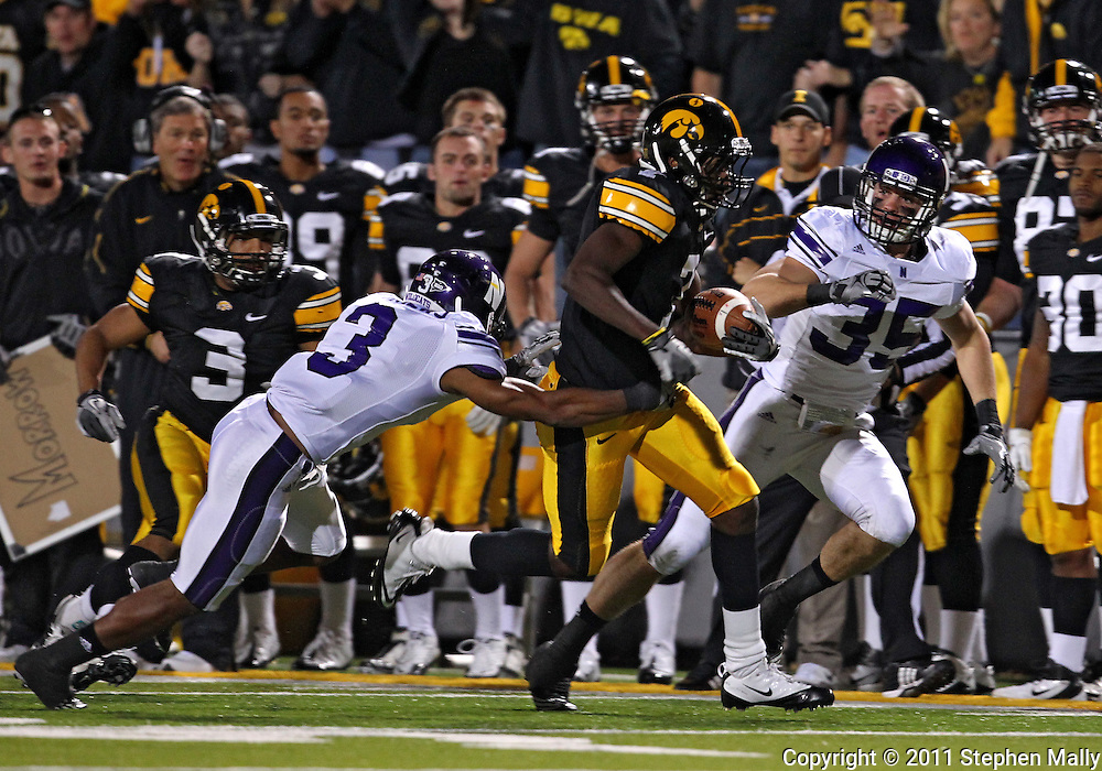 October 15, 2011: Iowa Hawkeyes wide receiver Marvin McNutt (7) is pulled down by Northwestern Wildcats cornerback Jeravin Matthews (3) on an onside kick attempt during the second half of the NCAA football game between the Northwestern Wildcats and the Iowa Hawkeyes at Kinnick Stadium in Iowa City, Iowa on Saturday, October 15, 2011. Iowa defeated Northwestern 41-31.