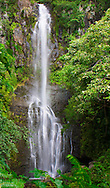 A waterfall cascades down the rocks along the Hawaiin coast