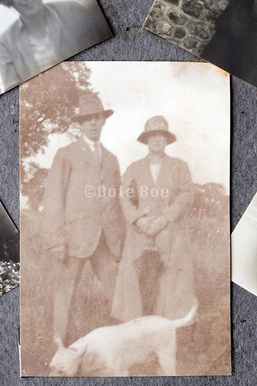 fading image of adult couple on a walking outing in photo album page early 1900s