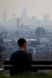 © licensed to London News Pictures. London, UK 01/04/2014. A man watching foggy London in Hampstead Heath on Tuesday, 1 April 2014 as The Met Office has forecast one of the year's worst smogs in London this week, following a combination of strong winds and powerful dust storms. Photo credit: Tolga Akmen/LNP