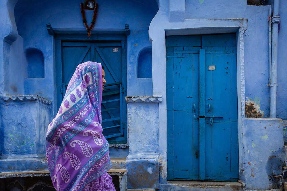 A woman in a purple sari with a purple veil passes in front of a traditional blue painted house.