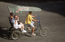 Tourists travelling on a cycle rickshaw in Havana; Cuba; filming scenery with a video camera,