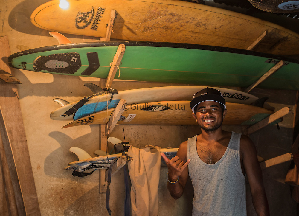 Rashed Alam, inside the garage in the yard of his house, proudly showing his surf boards. Cox's Bazar, Bangladesh