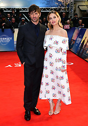 Michiel Huisman (left) and Lily James attending The Guernsey Literary and Potato Peel Pie Society world premiere held at Curzon Mayfair, London.