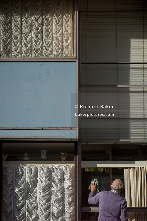 A resident of Bowater House on the Golden Lane Estate cleans a window, on 30th October 2017, in London, England. Residents on the Estate have erected banners by artists Jeremy Deller and Elizabeth Price to picket the developers. Banners on many balconies protest about the luxury apartment development called The Denizen, a controversial building by Taylor Wimpey that locals say will dominate their view and block their daylight.
