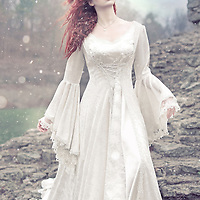 A powerful image of a young woman with wind and snow in her hair, wearing a white gown in a snowy outdoor atmosphere