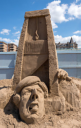 "© Licensed to London News Pictures. 12/05/2019. Weston-super-Mare, North Somerset, UK. The Weston-super-Mare Sand Sculpture Festival at Weston's beach. A Brexit related sand sculpture ""Off With My Head"" is worked on by Dutch artist Johannes Hogebrink. The sculpture depicts a large globe and in the centre of it is Theresa May putting her head under a falling guillotine, with Vladimir Putin and Donald Trump watching the spectacle of Brexit. The piece stands 4m tall and 6m wide and will take a total of 8 days to complete. The Weston Sand Sculpture Festival promises a new theme each year and this year the broad ""What If…?"" topic has allowed artists to create conceptual pieces of art portraying some important and alarming messages from Climate Change to Feminism. Photo credit: Simon Chapman/LNP"