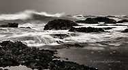 Black and white, rough water spills into tidal pools.