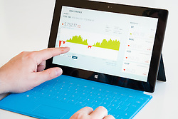 Man using BING financial application to check FTSE stock market performance on a Microsoft Surface rt tablet computer