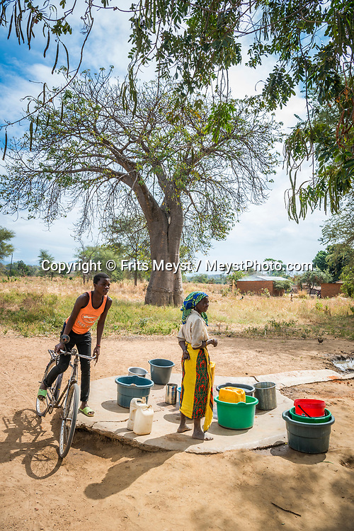 Malawi, July 2017. Women collect water at the well. The land between Lake Malawi and Liwonde National park is strewn with Baobab trees and small farming villages. Malawi is known for its long rift valley and the third largest lake in Africa: Lake Malawi. Malawi is populated with friendly welcoming people, who gave it the name: the warm heart of Africa. In the south the lake make way for a landscape of valleys surrounded by spectacular mountain ranges. Photo by Frits Meyst / MeystPhoto.com