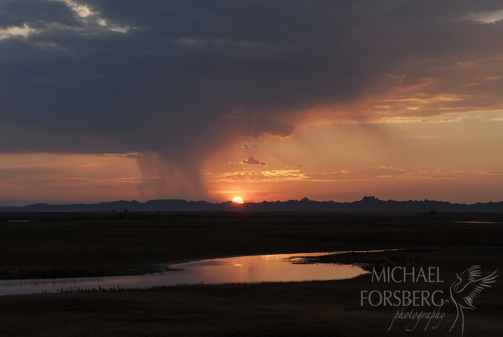Conata Basin, Buffalo Gap National Grassland, South Dakota..Sunset silhouettes isolated rain shower over temporary wetland in Conata Basin