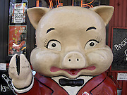 close up of a humorous piggy sculpture standing in front of a bar in New York City