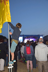 Latitude Festival, Henham Park, Suffolk, UK July 2018. Boy climbing one of the flag poles to get a better view of The Killers