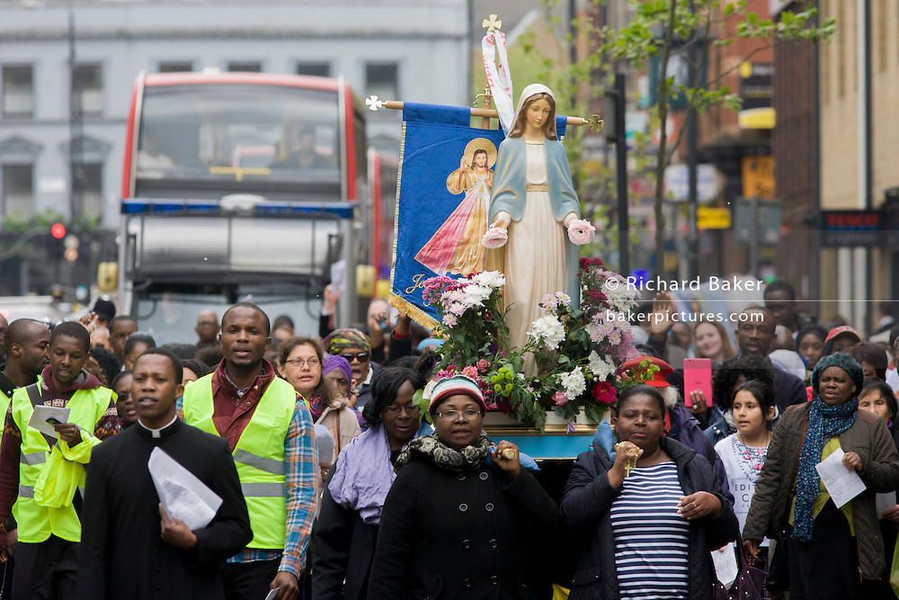 Christians carry an effigy of the Virgin Mary through the streets of the London borough of Lambeth. On the first Saturday of every May, traffic is stopped so about 100 parishioners can walk from St George's near Waterloo to the Catholic Sacred Heart of Jesus church in Camberwell.
