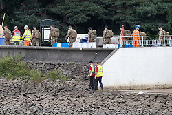 © Licensed to London News Pictures. 04/08/2019. Whaley Bridge, UK. 17 soldiers are seen crossing the reservoir . Watermarks on the rocks show the amount of water that has been pumped away since yesterday (Saturday 3rd August) . More rain is forecast today (Sunday 4th August) in the town of Whaley Bridge in Derbyshire after earlier heavy rain caused damage to the Toddbrook Reservoir , threatening homes and businesses with flooding. Photo credit: Joel Goodman/LNP