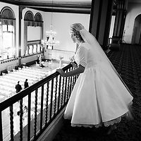 Alison peers out from a balcony as guests arrive to her wedding at Germania Place in Chicago, Illinois.