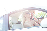 Happy female friends enjoying road trip in car on sunny day