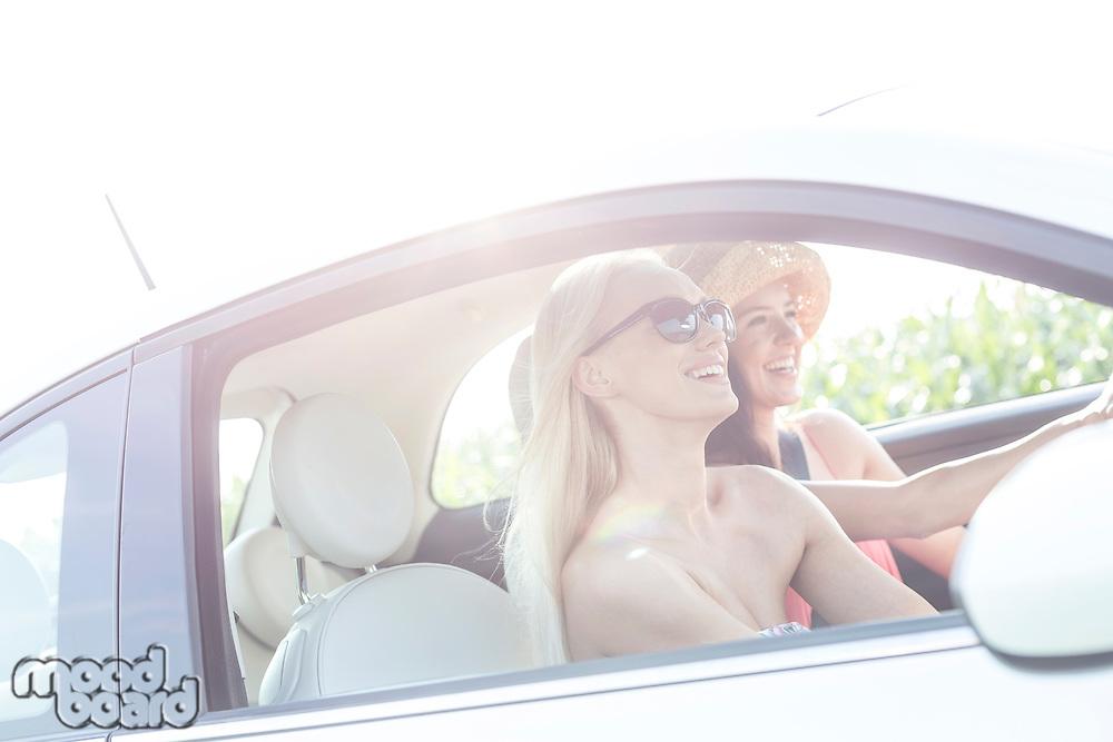 Happy female friends enjoying road trip in car on sunny day