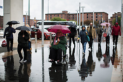 © Licensed to London News Pictures . 26/09/2016 . Liverpool , UK . Shoppers and tourists at Liverpool One shopping centre shelter under umbrellas as blustery showers end a spell of warm sunshine . Photo credit : Joel Goodman/LNP