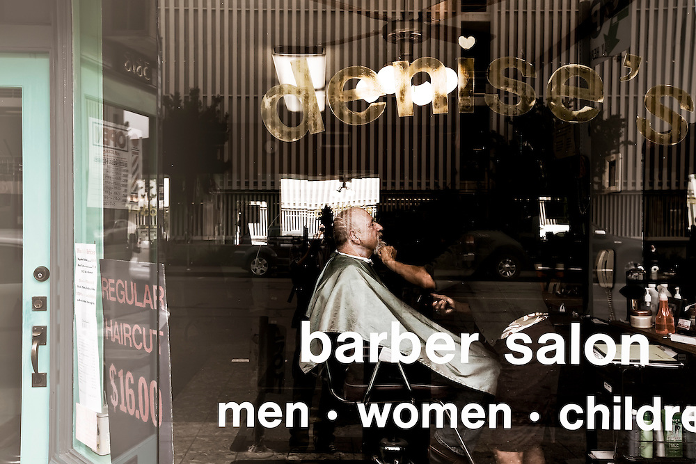 Man receives shave and a haircut at barber shop in Oakland, CA.  Copyright 2009 Reid McNally.