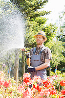 Male gardener watering plants at plant nursery